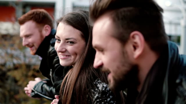 Two young men and a beautiful woman talk near bridge railing. Girl with dimples laughs cheerfully. Close-up, slow mo video