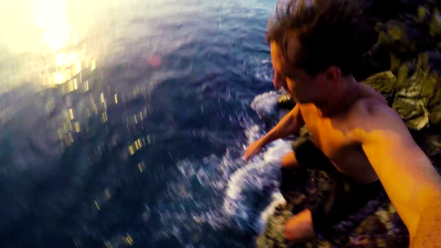 Two Young Men POV Cliff Jumping into Ocean Two Young Men POV Cliff Jumping into Ocean in Hawaii at Sunset. cliff jumping stock videos & royalty-free footage