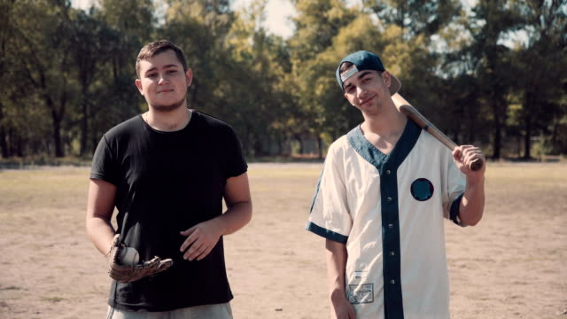 Two Young Men Heading to Play Baseball in Park video