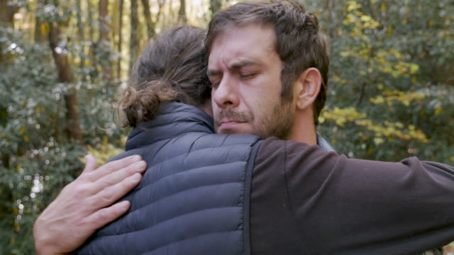 stockvideo's en b-roll-footage met twee jonge mannen knuffelen buiten in een park troostende elkaar tijdens de dag - funeral crying