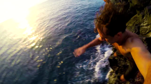 Two Young Men Jump off Cliff into Ocean Two Young Men Jump off Cliff into Ocean at Sunset (POV) cliff jumping stock videos & royalty-free footage