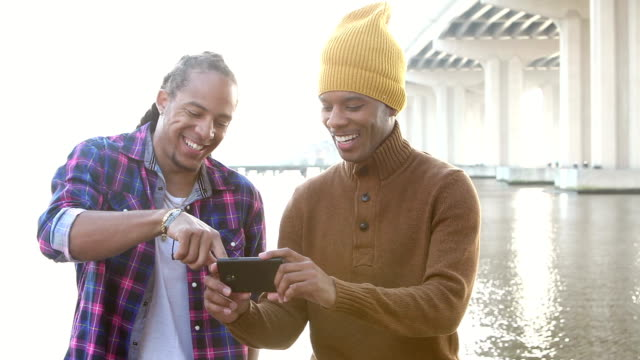Two young men on waterfront looking at mobile phone video