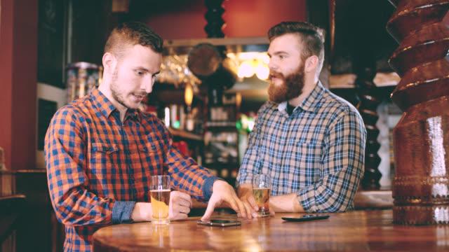 ds ms två unga män med en smartphone i puben - endast män bildbanksvideor och videomaterial från bakom kulisserna