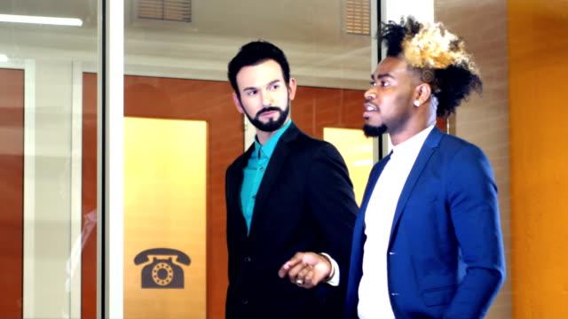 Two young multi-ethnic businessmen walking, talking