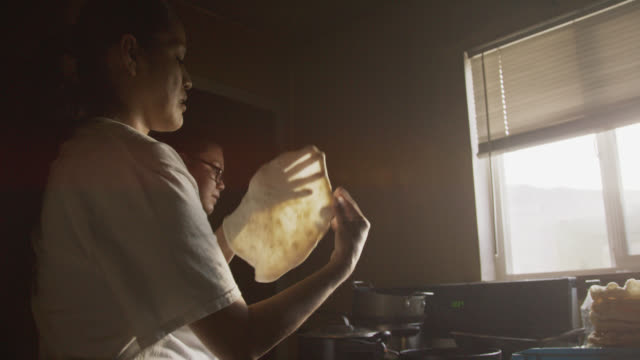 two young native american (navajo) women form and fry tortillas (fry bread) together in a kitchen indoors - płaski chleb filmów i materiałów b-roll