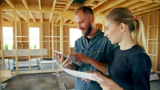 two young people discussing construction of a house - imprenditore edile video stock e b–roll