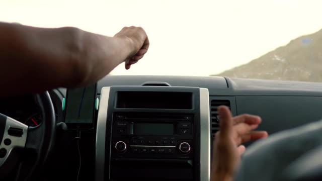 vidéos et rushes de deux jeunes gens écoutent de la musique dans la voiture. - homme faire coucou voiture