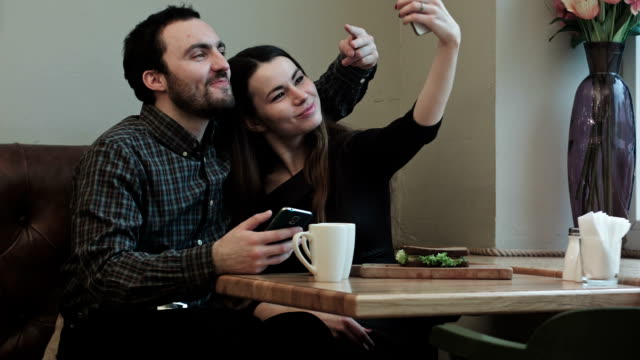 Two young people makeing selfy while in cafe video