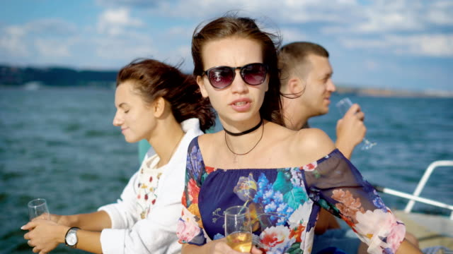 two young pretty brunettes are drinking champagne on a pleasure boat in summer day, looking and showing at a sea video