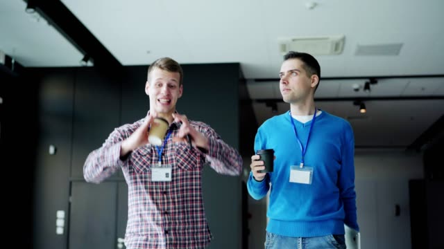 two young professionals with id cards walking down office hall and talking over coffee. business event attendees discussing work and looking around building at coffee break - badge video stock e b–roll