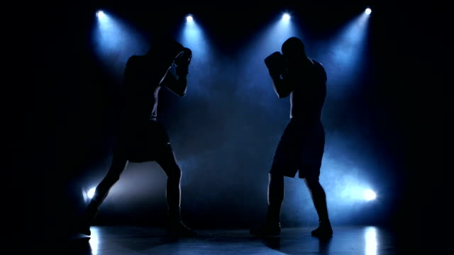 Two young sportsman are boxing in the studio video