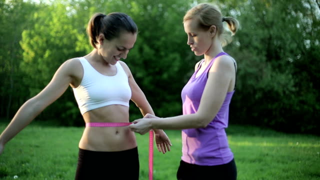 Two young sporty women measuring results of diet video