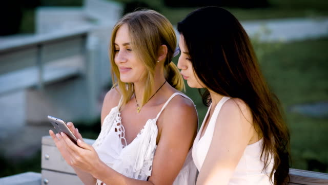 Two young stylish women sitting on bench and watching smartphone in summertime Two young stylish women sitting on bench and watching smartphone in summertime. Girls in white summer clothing sharing phone while posing on bench charming stock videos & royalty-free footage
