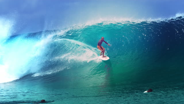 SLOW MOTION: Two young surfers watch their friend ride a huge barrel ocean wave. SLOW MOTION, CLOSE UP: Two young surfers watch their friend ride a huge barrel ocean wave glimmering in the sun. Pro surfboarders enjoying their summer holiday in Tahiti by riding epic tube waves. surf stock videos & royalty-free footage