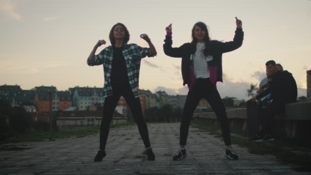 Two Young Teenager Girl Performing Modern Dance for their Friends on Abandoned Building. - vídeo