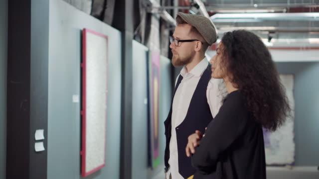 stockvideo's en b-roll-footage met twee jonge bezoekers van de kunsttentoonstelling bespreken een foto in een hal - bewondering