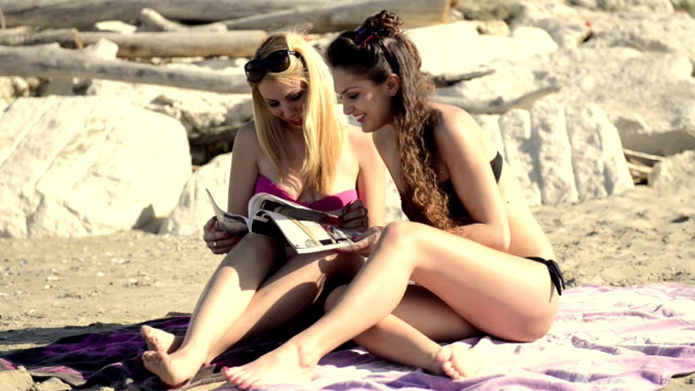 stockvideo's en b-roll-footage met two young woman at the seaside - newspaper beach
