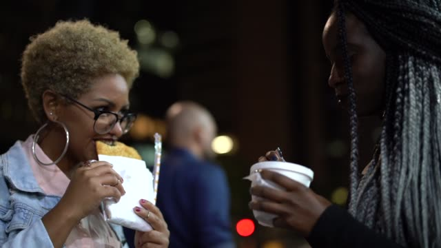 Two Young Woman Eating Pastel on the Street After Work
