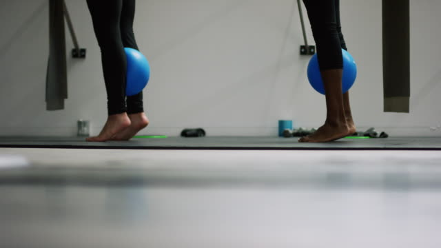 Two Young Woman (One Caucasian and the Other Asian Indian Ethnicity) Stand on Tiptoe with a Fitness Ball Between Their Calves in an Exercise Studio