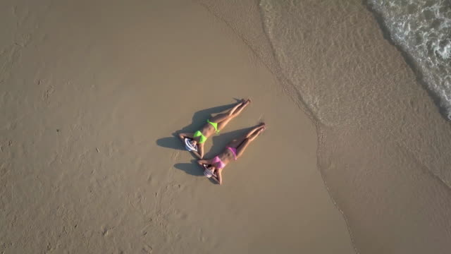 two young woman sunbathing on beach,aerial view - phuket video stock e b–roll