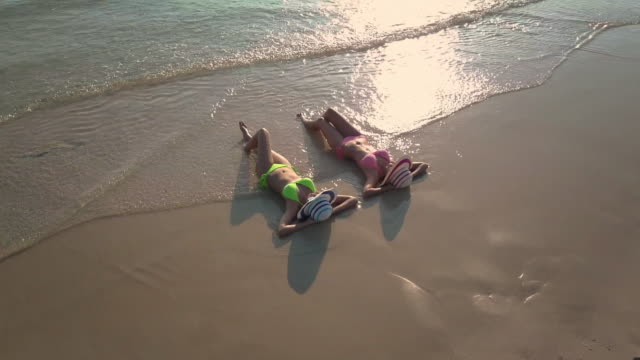 Two young woman sunbathing on beach,Aerial view Two young woman sunbathing on beach,Aerial view young singles stock videos & royalty-free footage