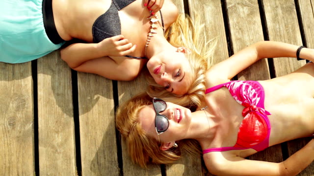 Two young woman sunbathing video