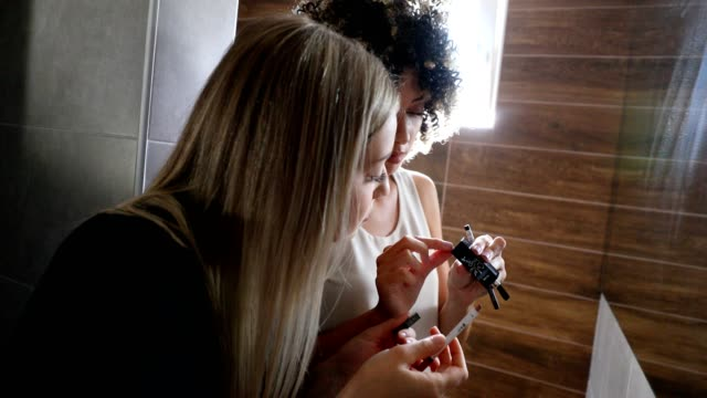 Two young women applying make-up in toilette Two young women applying make-up in toilette lip liner stock videos & royalty-free footage