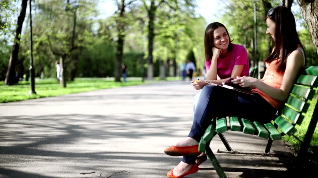 Two young women chatting on a park bench, tracking shot Two attractive university students study together on a bench, tracking shot park bench stock videos & royalty-free footage