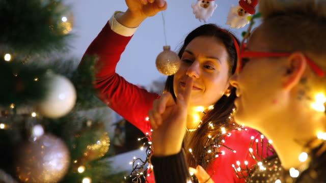 vídeos de stock, filmes e b-roll de duas mulheres jovens, decorar a árvore de natal. - decoração