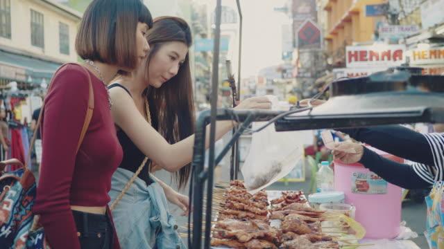 Two Young Women Enjoying Street Food in Khao San Road.
