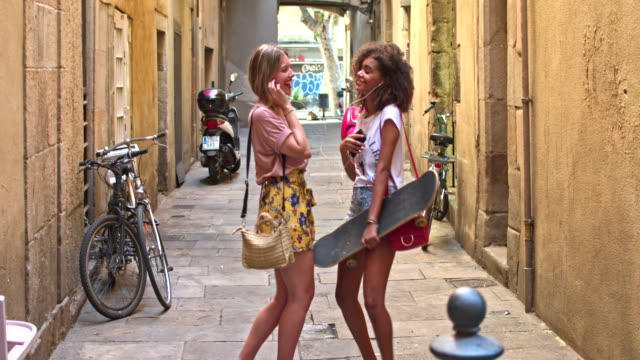 Two young women friends having fun sharing music in the street video