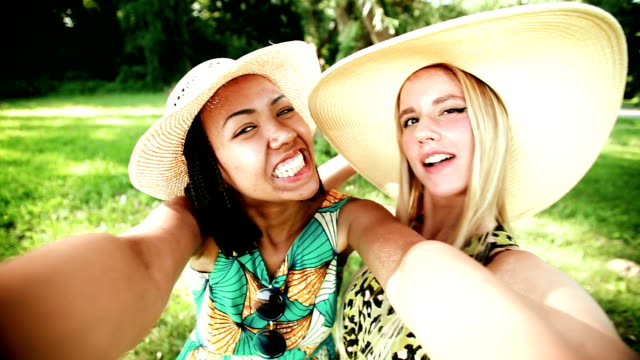 Two young women having fun while taking a selfie video