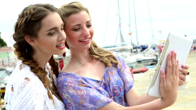 Two young women having fun with tablet video