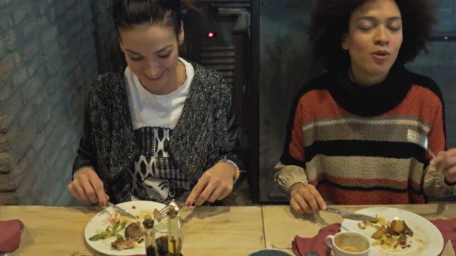 två unga kvinnor att ha lunch på en restaurang och kommunicera. - fritidskläder bildbanksvideor och videomaterial från bakom kulisserna