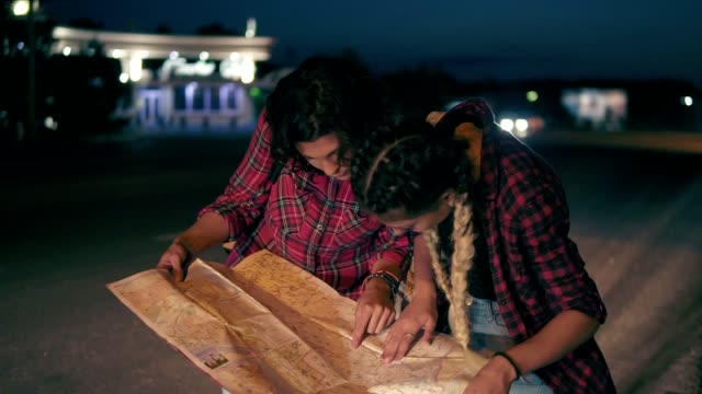 Two young women hitchhiker searching for direction looking at the map, young women hitch-hiking on a road in the city. Slowmotion shot video