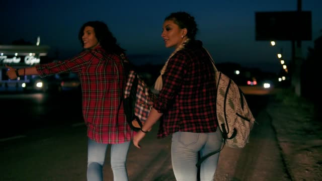 Two young women hitchhikers stand on the sidelines holding their backpacks and ask to stop the passing cars in the night in summertime. Slowmotion shot video