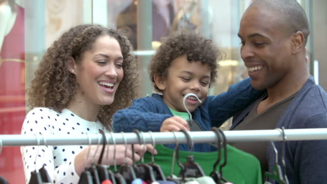 Two young women looking at clothes on rail in shopping mall.Shot on Sony FS700 at frame rate of 25fps Family looking at clothes on rail in shopping mall.Shot on Sony FS700 at frame rate of 25fps department store stock videos & royalty-free footage