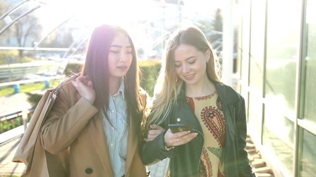 路上のスマート フォンに 2 つ若い女性 - テクノロジー ダイバーシティ 女性点の映像素材/bロール