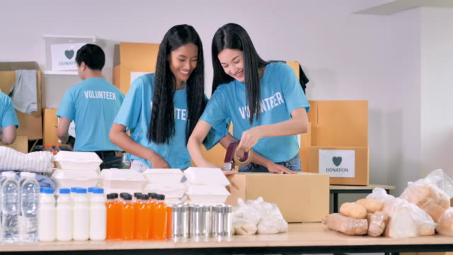 위기의 코로나바이러스 covid-19에서 아시아 인을위한 무료 음식 배달을 준비하는 자원 봉사자의 그룹 혼합 인종 의 두 젊은 여성. 우정, 팀워크, 성공, 자원 봉사자, 리더십, 사람들, 자선 개념. - giving tuesday 스톡 비디오 및 b-롤 화면