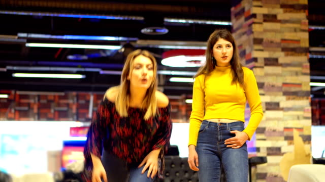 Two young women plays bowling video