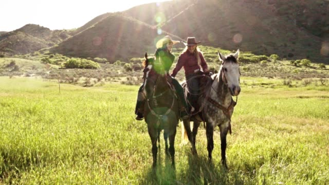 Two Young Women Riding Their Horses On The Open Range