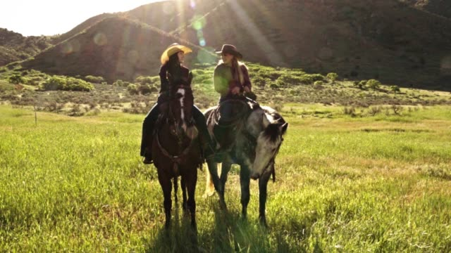 two young women riding their horses on the open range - cowgirl video stock e b–roll