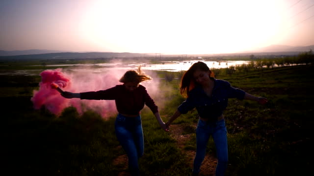 two young women runs and spins around with a pink smoke grenade, slow motion - jeans video stock e b–roll