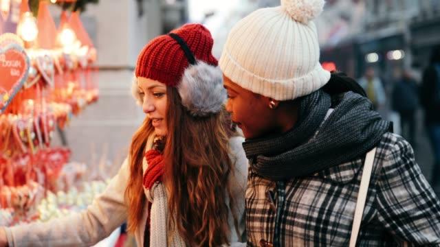 zwei junge frauen, die zu weihnachten einkaufen - weihnachtsmarkt stock-videos und b-roll-filmmaterial