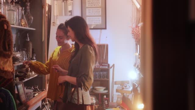 zwei junge frauen einkaufen in einem vintage antiquitätengeschäft - antique shop stock-videos und b-roll-filmmaterial