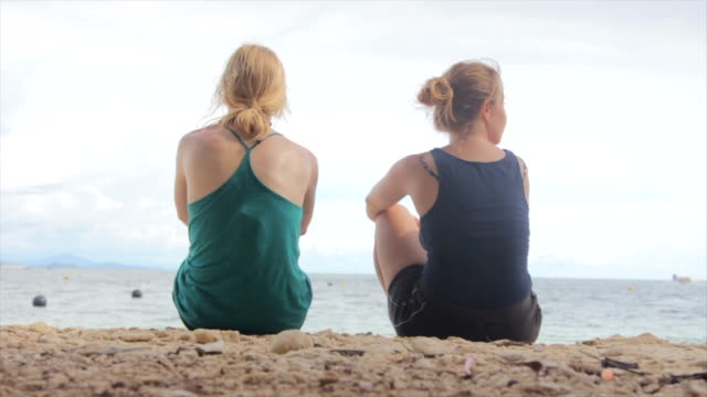 Two Young Women Sit on a Beach in Borneo video