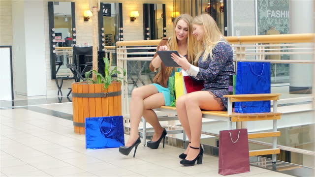 Two young women sitting with shopping bags and used Digital Tablet . Slow motion