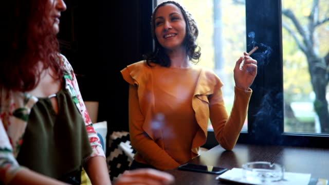 due giovani donne che fumano e si divertono al bar - sigaretta video stock e b–roll
