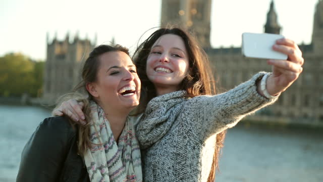 2人の若い女性がロンドンのウェストミンスター宮殿の前でスマートフォンの自分撮りをします。 - 兄弟姉妹点の映像素材/bロール