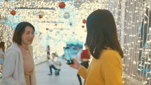 Two young women taking photo with a mobile phone with lights decorated at Christmas